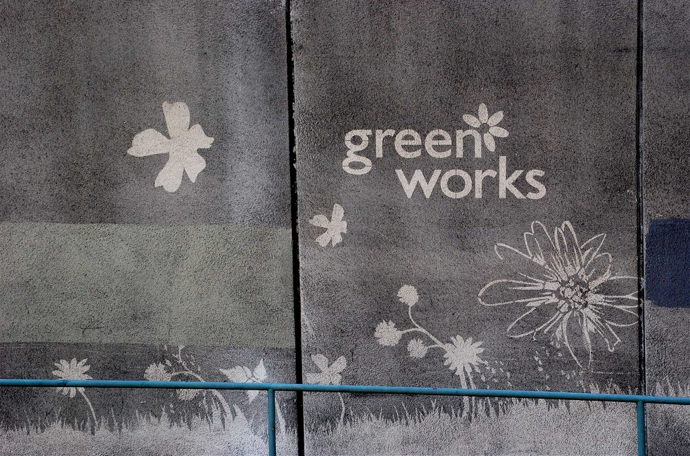 Dirty pavements with a stencil of clean pavement showing the Green Works logo and a grass and flowers design